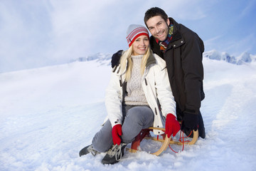 Couple sitting on sled in the snow