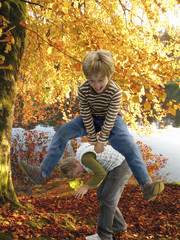 Boys playing leapfrog near lake in autumn