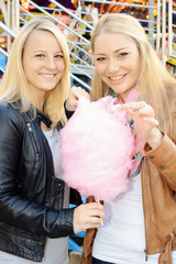 Frauen essen Zuckerwatte auf Rummelplatz