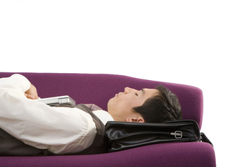 Businessman using briefcase as pillow, asleep on sofa, close-up, cut out