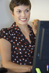 Businesswoman eating sandwich at desk, using computer, smiling