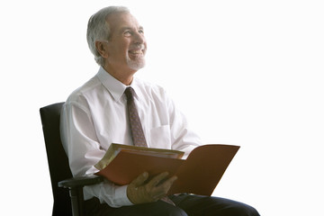 Senior businessman reviewing paperwork, cut out