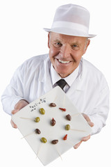 Sales clerk displaying specialty olives, cut out