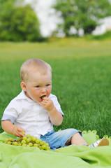 Little boy eats grapes