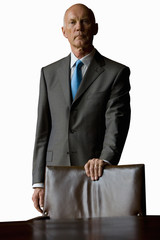 Portrait of businessman with hand on chair, cut out