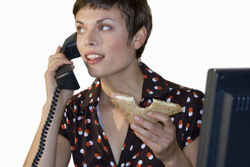 Businesswoman eating sandwich, using telephone, smiling, cut out