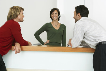 Two businessmen flirting with receptionist at reception desk, smiling