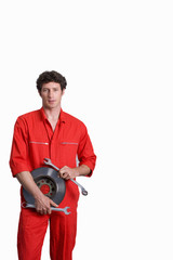Male car mechanic, in red overalls, holding vehicle part and wrenches, smiling, portrait, cut out