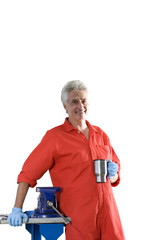 Mature male car mechanic, in red overalls, taking tea break, smiling, portrait, cut out