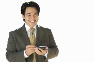 Businessman using electronic organiser, smiling, portrait, cut out