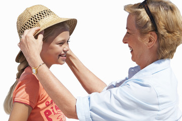 Grandmother placing sun hat on granddaughter's head, smiling, side view, cut out