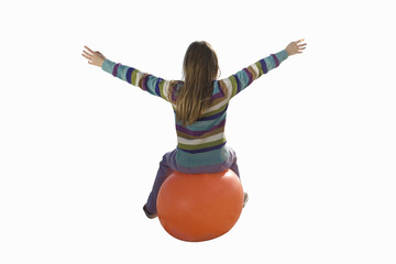 Girl on inflatable hopper, arms outstretched, rear view, cut out