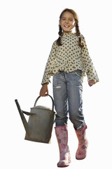 Girl in pink wellingtons carrying watering can, smiling, portrait, cut out