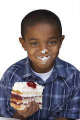 Boy eating slice of cream cake, smiling, close-up, portrait, cut out