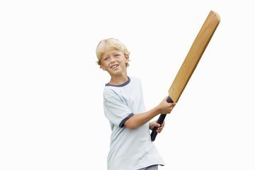 Blonde boy playing cricket, swinging bat, smiling, cut out