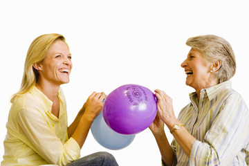 Senior woman and adult daughter inflating balloons, laughing, side view, cut out