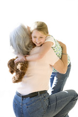 Grandmother and granddaughter embracing in airport, girl holding soft toy, smiling, cut out