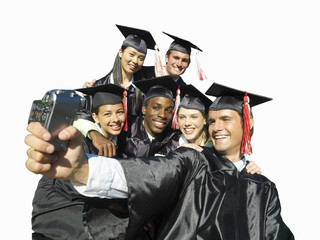 Graduates in caps and gowns taking photograph of themselves, cut out