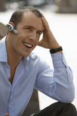 Businessman wearing mobile phone hands-free device on ear, smiling, close-up, outdoors