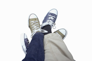 Couple wearing plimsoles, legs entwined, cut out