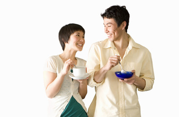 Young couple standing with breakfast, smiling at each other, cut out