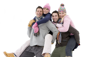 Two young couples in winter clothing, portrait, men carrying women on backs, cut out