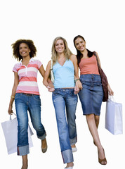 Three young women walking hand in hand with shopping bags, smiling, low angle view, cut out