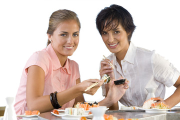 Two women eating sushi, smiling, portrait, cut out