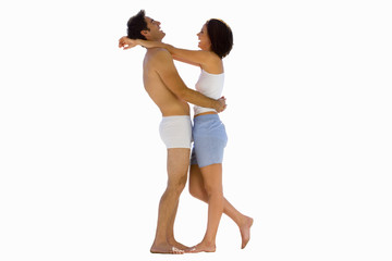 Young couple in underwear embracing, side view, cut out