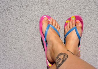Tanned legs with tattoos in flip-flops