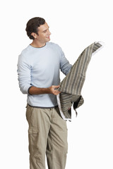 man holding and considering piece of fabric, cut out