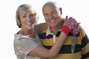 senior couple hugging, wearing gardening gloves, cut out