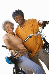 senior couple on bicycles wearing bicycle helmet, cut out