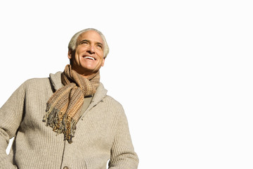 senior man in scarf looking up at sky, cut out