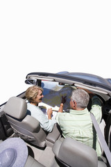 senior couple looking at map in convertible car, cut out
