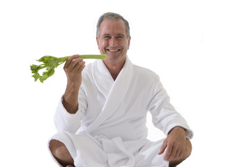 senior man in robe eating celery, cut out