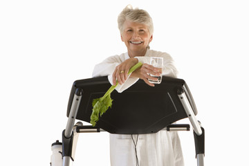 senior woman leaning on gym equipment in robe, cut out