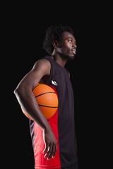 Basketball player standing with a basket ball on black backgroun