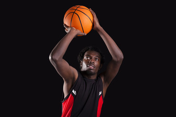 Basketball player dunking on black background