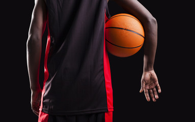 Rear view of a basketball player standing with a basket ball on
