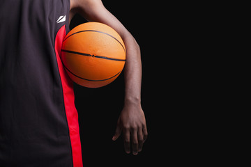 Basketball player standing with a basket ball on black backgroun