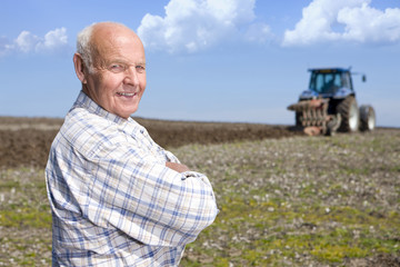 Farmer standing in field with tractor and plough in background