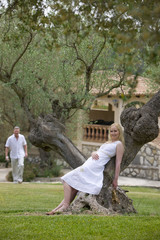 Smiling woman leaning on olive tree trunk with man in background