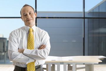 Smiling businessman standing with arms crossed in empty office