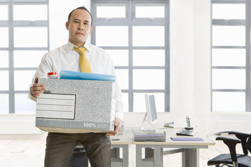 Businessman holding box of belongings in office