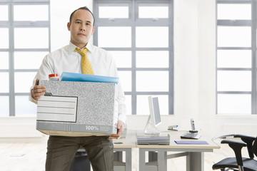 Businessman holding box of belongings in office