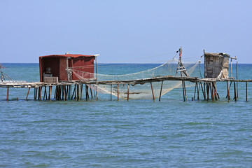 pier with fishing net and hut