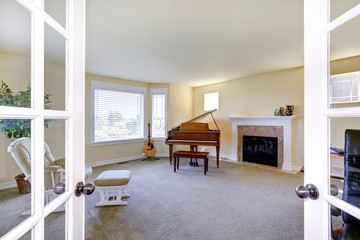 Room with fireplace, grand piano and guitar