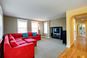 Living room with bright red couch and TV