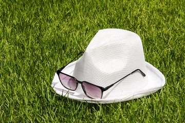 white hat and sunglasses on the green grass background